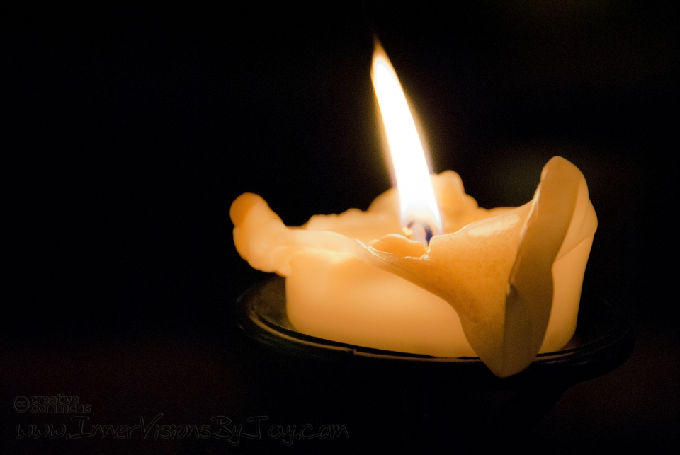 Candle burning down against black background