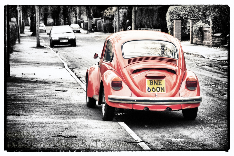Selective color red volkswagen beetle parked on winter curb