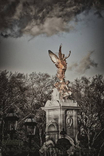 Selective color gold statue against roiling storm clouds
